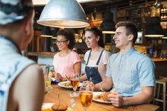 Amis heureux mangeant et buvant à la barre ou au bar Images stock