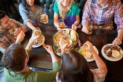 Amis heureux mangeant et buvant à la barre ou au bar Photo libre de droits