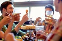Amis heureux mangeant et buvant à la barre ou au bar Photographie stock libre de droits
