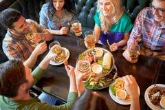 Amis heureux mangeant et buvant à la barre ou au bar Images libres de droits