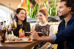 Amis heureux mangeant et buvant à la barre ou au café Image stock