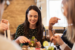 Amis heureux mangeant et buvant à la barre ou au café Photographie stock