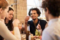 Amis heureux mangeant et buvant à la barre ou au café Photo stock