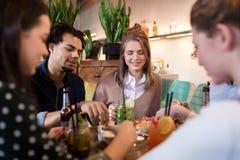 Amis heureux mangeant et buvant à la barre ou au café Images libres de droits