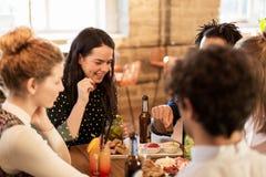 Amis heureux mangeant et buvant à la barre ou au café Images stock