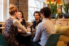 Amis heureux mangeant et buvant à la barre ou au café Photos stock