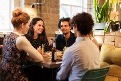 Amis heureux mangeant et buvant à la barre ou au café Photo libre de droits