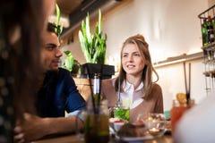 Amis heureux mangeant et buvant au restaurant Photographie stock