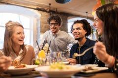 Amis heureux mangeant et buvant au restaurant Image libre de droits
