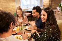 Amis heureux mangeant et buvant au restaurant Photos stock