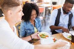 Amis heureux mangeant et parlant au restaurant Photo stock