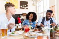 Amis heureux mangeant et parlant au restaurant Photos stock