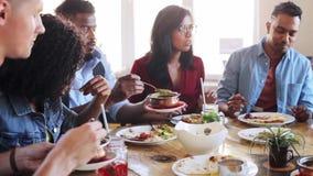 Amis heureux mangeant et parlant au restaurant banque de vidéos