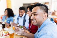 Amis heureux mangeant et parlant au restaurant Image stock