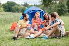Amis heureux mangeant la pastèque au camping Images stock