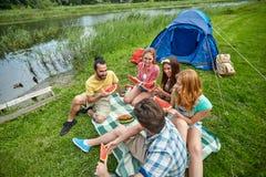 Amis heureux mangeant la pastèque au camping Image stock