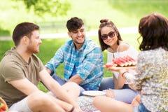 Amis heureux mangeant la pastèque au pique-nique d'été Photographie stock