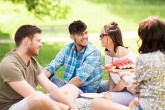 Amis heureux mangeant la pastèque au pique-nique d'été Images libres de droits