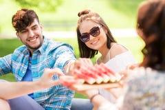 Amis heureux mangeant la pastèque au pique-nique d'été Photographie stock libre de droits
