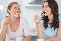 Amis heureux mangeant le gâteau et ayant le café Image libre de droits