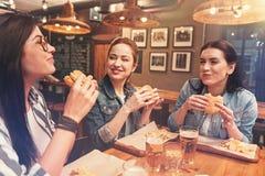 Amis heureux mangeant leurs hamburgers Photographie stock