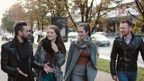 Amis heureux marchant à la rue Hommes beaux et deux jolies filles causant sur l'aller Tir de Steadicam, MOIS lent banque de vidéos
