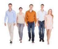 Amis heureux marchant au-dessus du fond blanc Photo stock