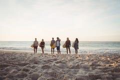 Amis heureux marchant avec des planches de surf Image libre de droits