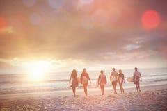 Amis heureux marchant avec des planches de surf Images stock