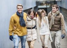 Amis heureux marchant ensemble dans la ruelle Photo stock