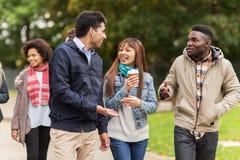Amis heureux marchant le long du parc d'automne Photo stock