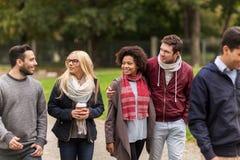 Amis heureux marchant le long du parc d'automne Photographie stock