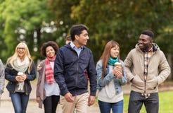 Amis heureux marchant le long du parc d'automne Image libre de droits