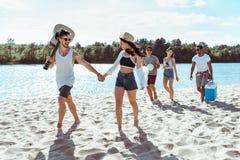 Amis heureux marchant sur la plage le jour d'été Photos stock