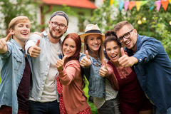 Amis heureux montrant des pouces au jardin d'été Photos stock