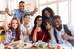 Amis heureux montrant des pouces au restaurant Photo libre de droits