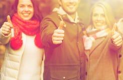 Amis heureux montrant des pouces dans le parc d'automne Photos stock