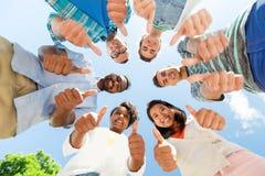 Amis heureux montrant des pouces se levant dans le cercle Image libre de droits