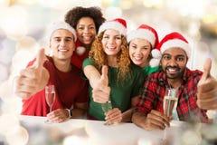 Amis heureux montrant des pouces vers le haut de Noël à la partie Photos libres de droits