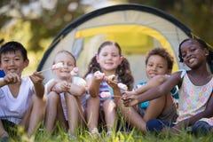 Amis heureux montrant des sucreries tout en se reposant par la tente au terrain de camping Photos libres de droits
