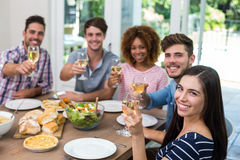 Amis heureux montrant le vin tout en ayant le repas Photos libres de droits