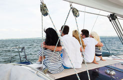 Amis heureux naviguant et s'asseyant sur la plate-forme de yacht Photographie stock libre de droits