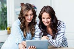 Amis heureux observant la vidéo sur le comprimé numérique Image stock