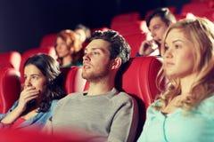 Amis heureux observant le film d'horreur dans le théâtre Photos stock