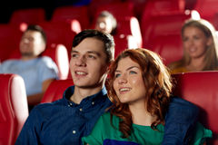 Amis heureux observant le film dans le théâtre Photo stock