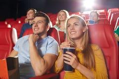 Amis heureux observant le film dans le théâtre Images libres de droits