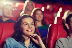 Amis heureux observant le film dans le théâtre Image stock