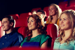 Amis heureux observant le film dans le théâtre Images stock