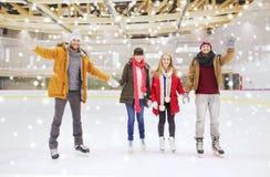 Amis heureux ondulant des mains sur la piste de patinage Image stock