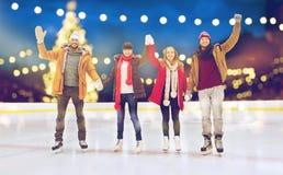 Amis heureux ondulant des mains sur la piste de patinage extérieure Photo libre de droits